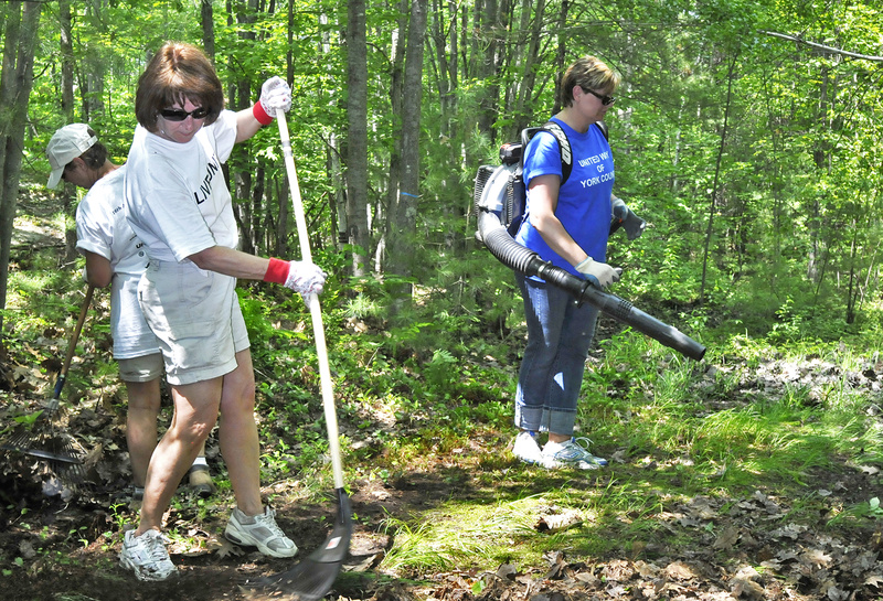 Ellen Murphy rakes while Michelle Sawyer operates a leaf blower during a Day of Caring at the Biddeford YMCA. A crew of about 60 volunteers helped clean up trails, repaint signs and benches, and clear out brush, among numerous other tasks.
