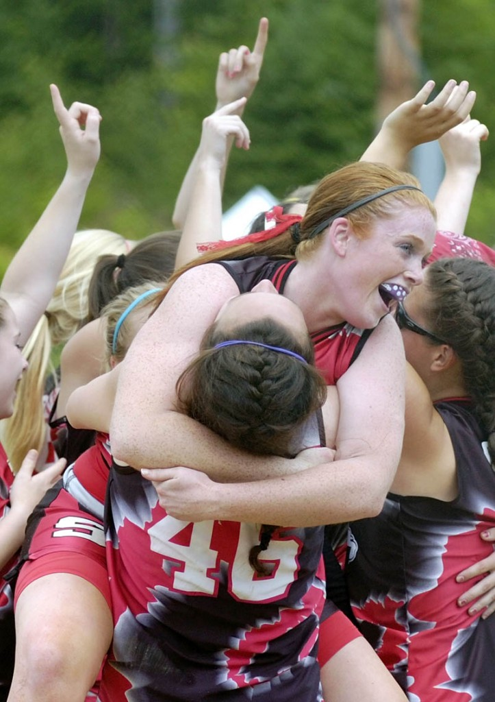 Scarbourough pitcher Maureen Hannan ,center, is hugs teammate Marisa O'Toole as the Red Storm their victory over the Messalonskee High School team after the last out of the Class A state championship softball game on today at Cony Family Field in Augusta. Scarborough blanked the Eagles 5-0.