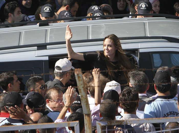 Angelina Jolie waves as she exits a van surrounded by Syrian refugees at the Altinozu refugee camp near the Syrian border today.