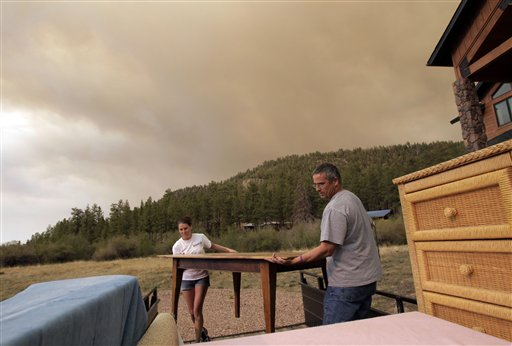 Jim Tress, right, and his daughter Samantha move furniture as they evacuate their home in Greer, Ariz., Saturday, June 4, 2011. Firefighters are working to contain the third largest fire in state history, with its smoke visible in parts of southern Colorado. Fire officials said they had zero containment of the fire near the New Mexico-Arizona state line, which has forced an unknown number of people to evacuate.