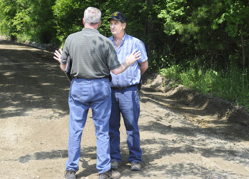 DIG IT: Dennis Hayden, left, of the Maine Public Utilities Commission damage prevention program advises Marshall Swan to stop grading the Tasker Road in Chelsea Wednesday morning. Swan was awarded a bid to grade eight dirt roads in the community. Hayden advised Swan that he violated state dig safe laws by grading without a permit.
