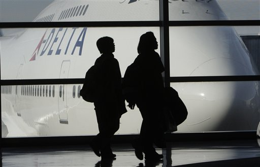 In this Jan. 21, 2010 file photo, passengers walk past a Delta Airlines 747 aircraft in McNamara Terminal at Detroit Metropolitan Wayne County Airport in Romulus, Mich. Reacting to public outcry, Delta said Wednesday, June 8, 2011, it will allow members of the military to check four bags for free. The news came after two Army soldiers returning from Afghanistan complained in an online video that Delta charged their unit a total of $2,800 when some of them checked a fourth bag.(AP Photo/Paul Sancya, file)