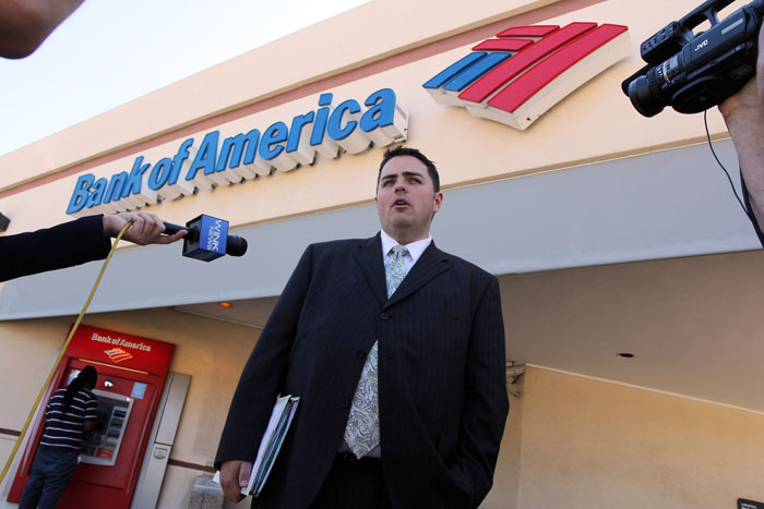 Todd Allen, attorney for Warren and Maureen Nyerges, speaks to the media outside a Bank of America branch in Naples, Fla., last week while deputies meet with the bank manager inside. Bank of America tried to foreclose on the Nyerges' fully-paid-for home last year, starting a legal battle with the couple, who had paid cash for the home in 2009.