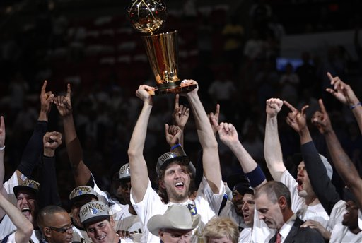 Dallas Mavericks' Dirk Nowitzki holds up the championship trophy after Game 6 of the NBA Finals basketball game against the Miami Heat Sunday in Miami. The Mavericks won 105-95 to win the series.
