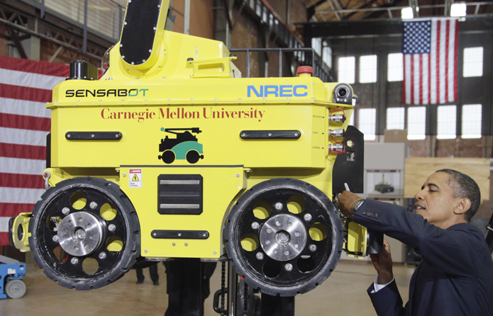 President Barack Obama signs a robot after speaking at Carnegie Mellon University in Pittsburgh today.