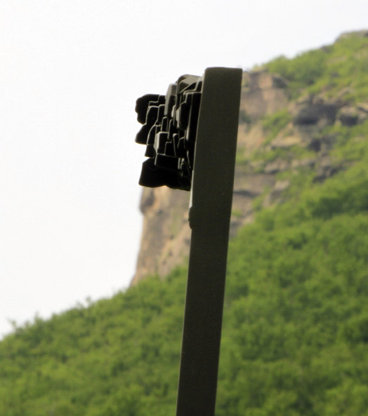 One of seven sculptures of the Old Man line up with the position the granite formation once occupied on Cannon Mountain.