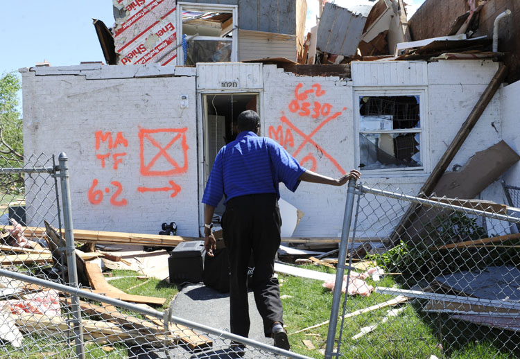 A man enters his home today, a day after a tornado struck iSpringfield, Mass. Two late-afternoon tornadoes shocked emergency officials Wednesday with their suddenness and violence and caused the state's first tornado-related deaths in 16 years.
