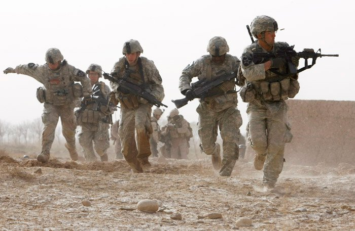 A U.S. soldier returns fire as others run for cover during a firefight with insurgents in Helmand province, southern Afghanistan, in this February 2010 photo.