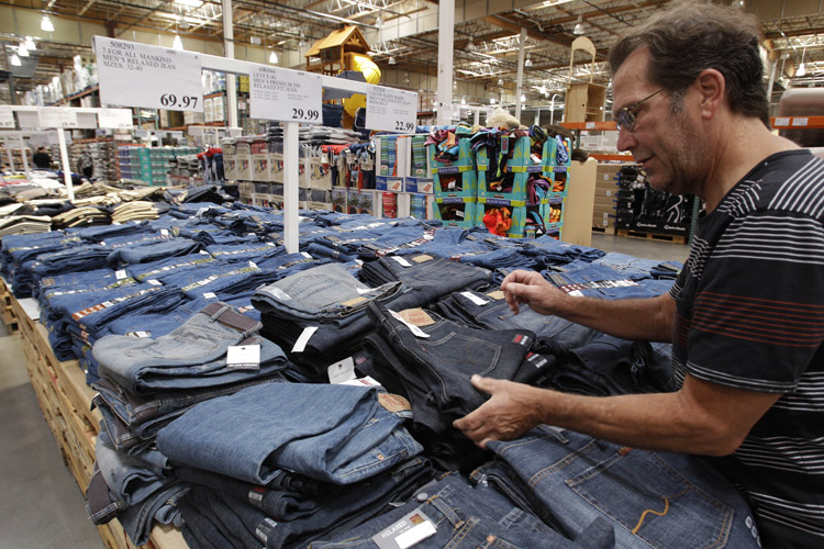 A shopper looks at Levi jeans at Costco in Mountain View, Calif., recently. Wholesale prices rose at the slowest pace in 10 months in May as food costs fell and gas prices rose by the smallest amount in eight months.