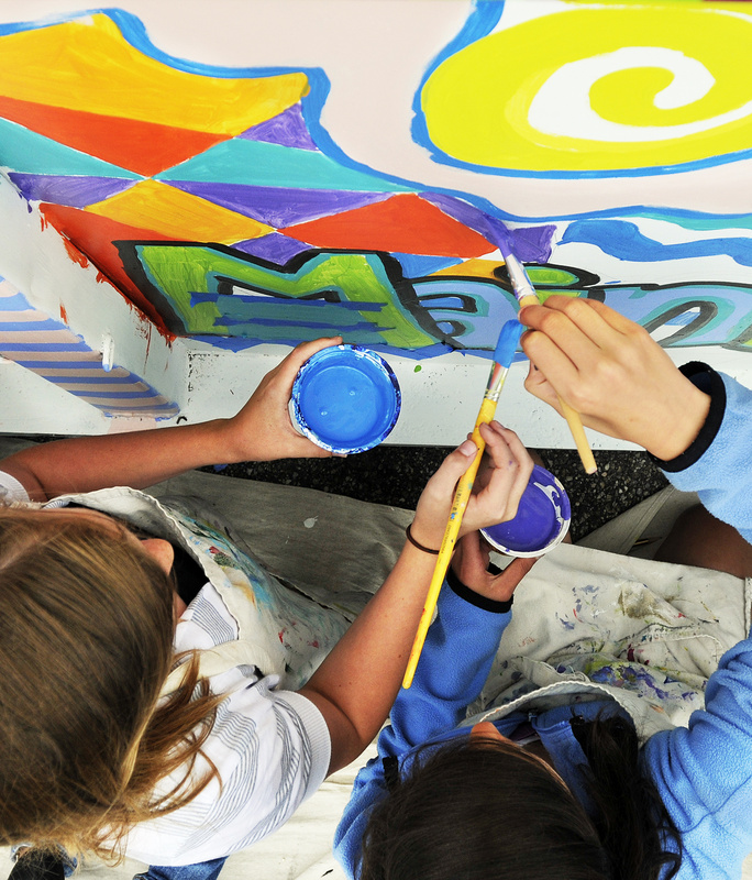 Madi Connolly and Monika Scheindel add their artistic touches to the recycling cause.
