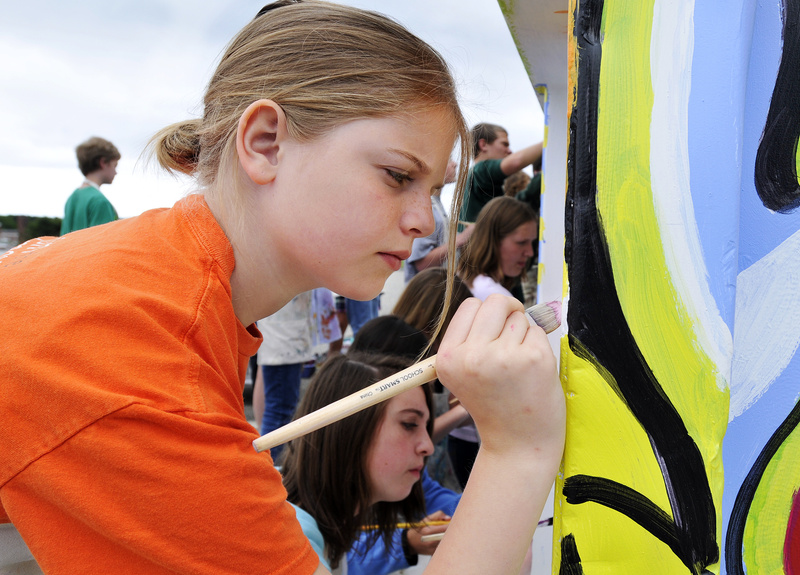 Megann Sullivan, a 7th grader, joins in painting a recycling container on Monday outside Cape Elizabeth Middle School. Two students, Addy Graessle and Lexi Demeter, won an ecomaine design contest, giving the school $500 to paint the bin.