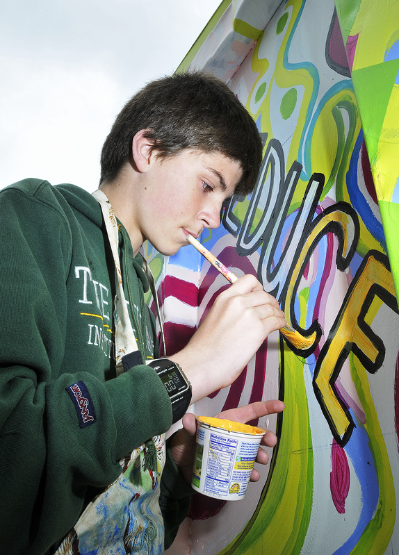 Tim Corsello paints letters on the container to encourage recycling.