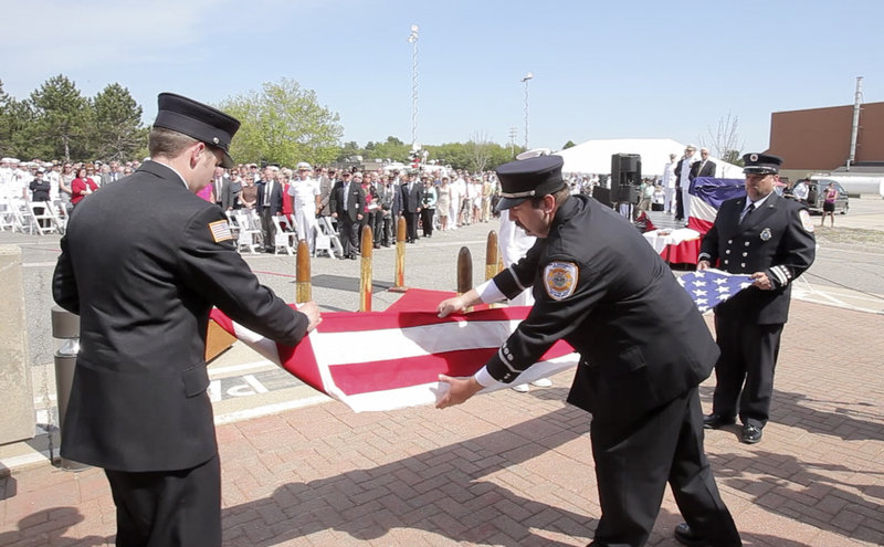 From left, Ian Canavan, Jim Backman and Bill Price, firefighters with the Brunswick Naval Air Station, take down the American flag for the last time during a disestablishment ceremony at the base Tuesday.