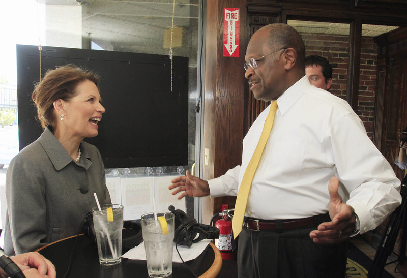 Rep. Michele Bachmann, R-Minn., runs across a fellow GOP presidential hopeful, businessman Herman Cain, at a radio show taping Tuesday in Concord, N.H. Bachmann also fielded media questions about another potential competitor, Sarah Palin.