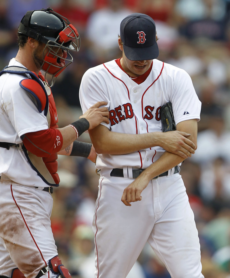 Rich Hill of the Red Sox is assisted by catcher Jarrod Saltalamacchia after injuring his forearm in the seventh inning.