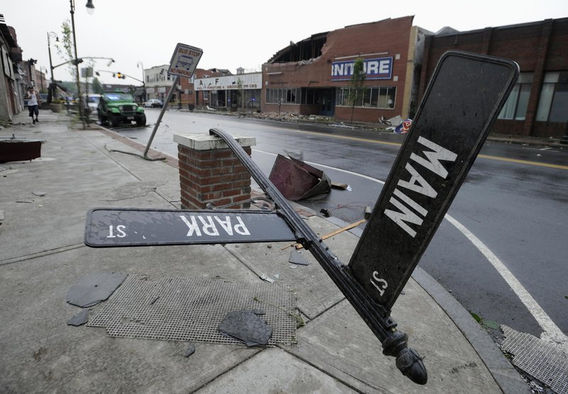 A toppled street sign and a damaged brick building attest to the severity of the winds that hit Springfield on Wednesday. Dozens of injuries were reported. State police received numerous calls about tornado sightings, and power outages hit at least 48,000 customers.