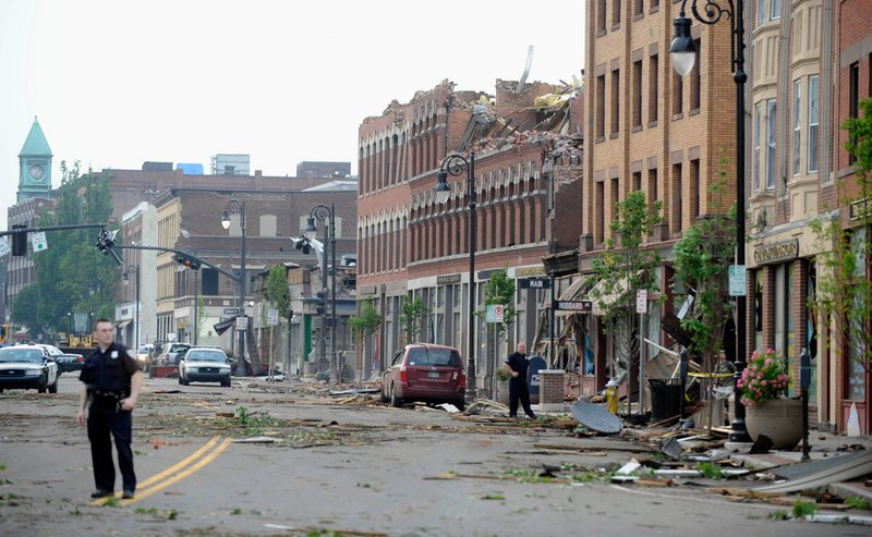 """Debris litters Main Street in Springfield, Mass., on Wednesday, after the top floor of a building on the street was shorn off by a tornado. One office worker reported a """"massive cloud of debris floating around in a circular, cylindrical fashion."""""""