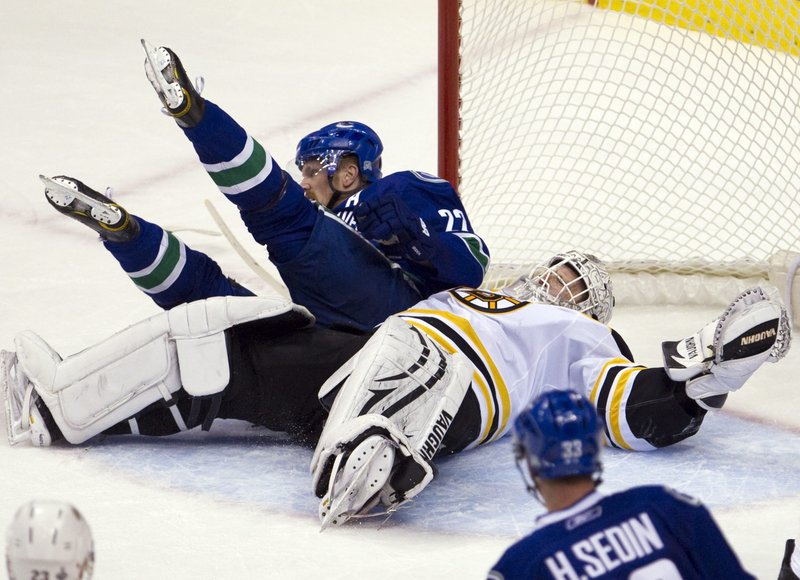 Boston goalie Tim Thomas lies sprawled on the ice with Vancouver's Daniel Sedin on top during the Canucks' 1-0 win in Game 1 of the Stanley Cup on Wednesday.