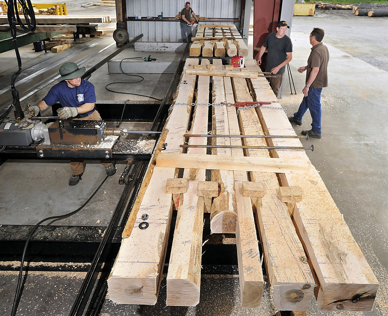 Thomas Thayer, left, drills holes in hardwood timbers for bolts that will hold the mat together. Others working the project are Denis Couture and Shawn Brown. Owner Fred Decker is at right.