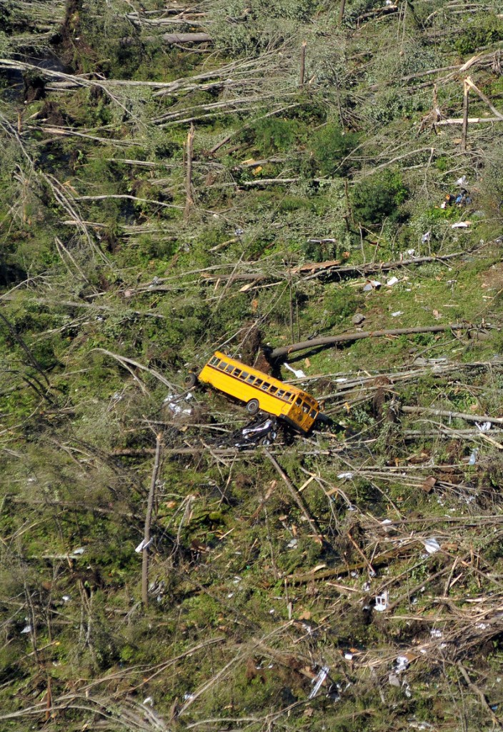 In the aftermath of Wednesday's violent tornados, this aerial photo in Brimfield, Mass., shows a school bus overturned by high winds, surrounded by knocked-down trees at the Village Green Family Campground. At least three people died – the state's first tornado-related deaths in 16 years.