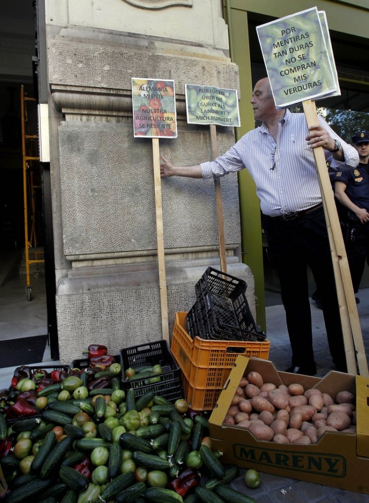 "A farmer places a placard reading ""Because of such big lies, nobody is buying my vegetables"" as protesting farmers dump some 700 pounds of cabbage, tomatoes, peppers, cucumbers and other produce outside the German consulate in Valencia, Spain, on Thursday."