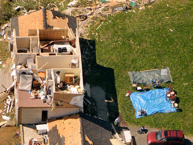 Homeowners in Brimfield, Mass. collect their belongings on tarps outside their house on Thursday. Residents in 19 Massachusetts communities were affected by late-afternoon tornadoes Wednesday, storms that shocked officials with their suddenness and violence.