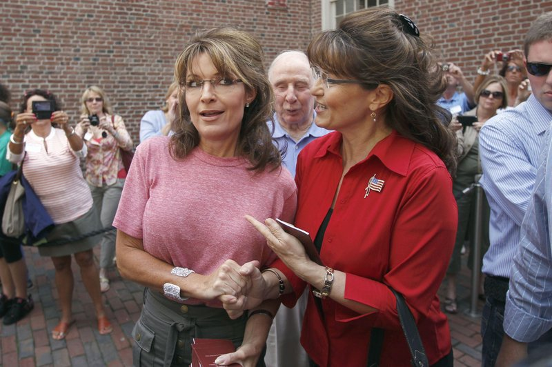 Former Alaska Gov. Sarah Palin, left, poses with celebrity impersonator Cecilia Thompson during a tour of Boston's North End neighborhood on Thursday.
