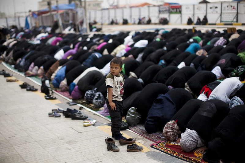 A boy stands as women pray in Benghazi, Libya, on Friday. Rebel forces had reportedly been making gains in western towns Friday.