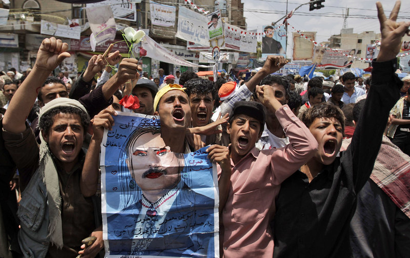 Anti-government protesters hold a defaced poster of Yemeni President Ali Abdullah Saleh as they demand his resignation in San'a, Yemen, on Saturday.