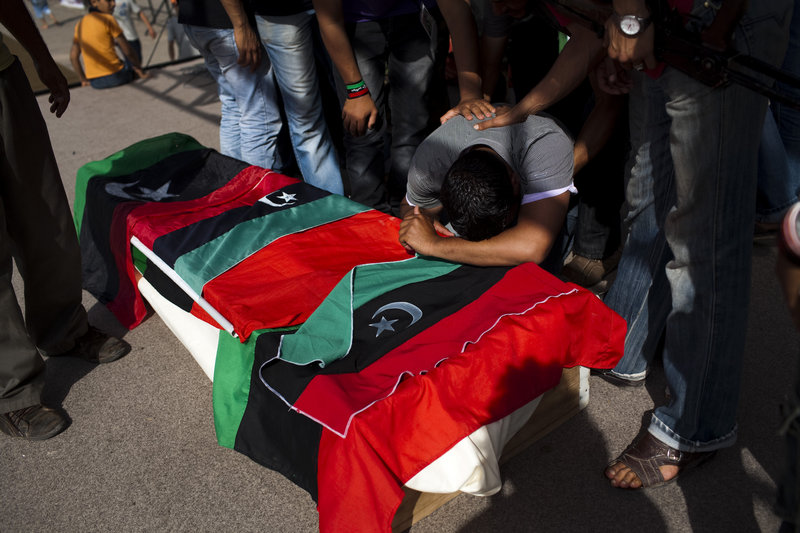 A man mourns on the coffin of a rebel fighter killed in the front line against Moammar Gadhafi's forces, during a burial in the rebel stronghold of Benghazi, Libya, on Saturday.