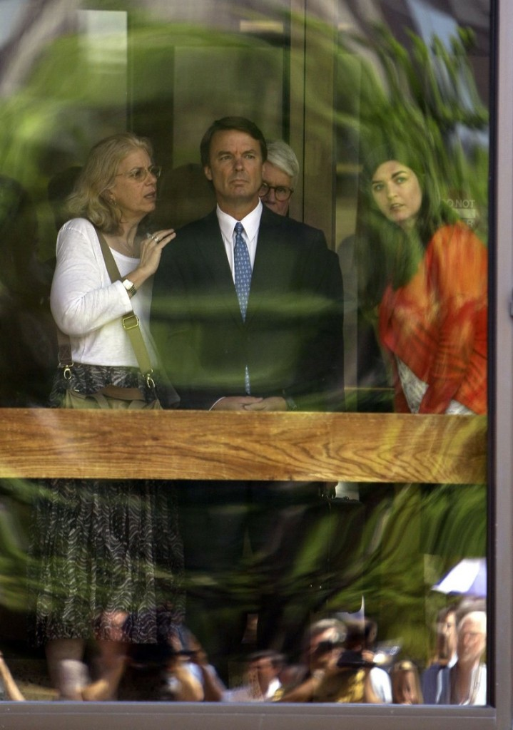 Former presidential candidate John Edwards and his daughter Cate, right, peer out of the federal building following a court appearance in Winston-Salem, N.C., on Friday. The woman at left is unidentified.