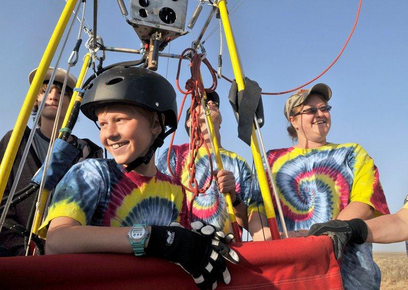 Bobby Bradley, 9, of Albuquerque, N.M., smiles after landing his hot air balloon after a solo flight near Tome, N.M., on Saturday. Behind him in tie-dyed shirts are his father, Troy Bradley, and mother, Tami Bradley.