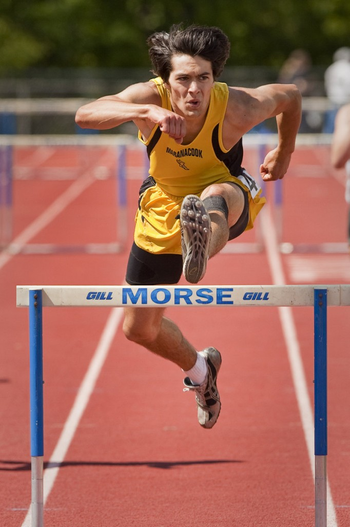 Tyler Watson of Maranacook has his eyes down the track as he clears the final barrier on his way to a victory in the Class C 300-meter hurdles