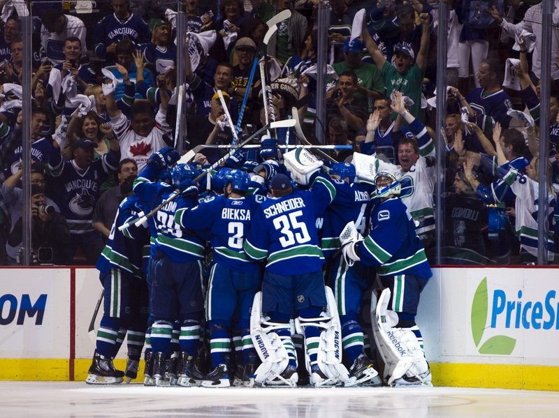 Vancouver players celebrate after Alex Burrows scored 11 seconds into overtime as the Canucks beat the Bruins 3-2 in Game 2 of the Stanley Cup finals.