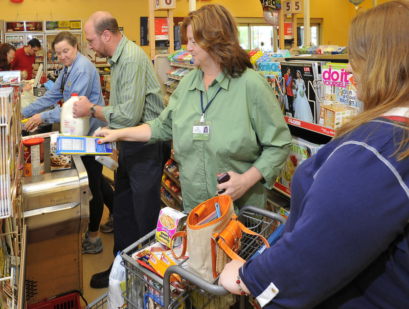 Ray Routhier helps community support worker Lisa Mace, center, and Ami Arbassio, right, check out groceries at a Hannaford in South Portland.