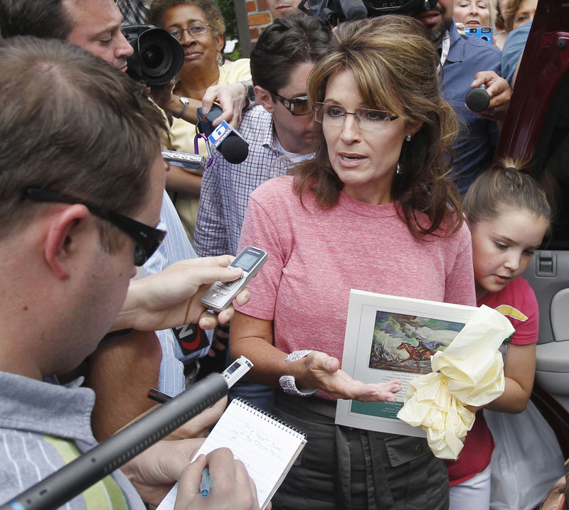 """Former Alaska Gov. Sarah Palin, holding a booklet depicting Paul Revere, visits Boston's North End during her """"One Nation"""" bus tour last Thursday. At right is her daughter Piper."""