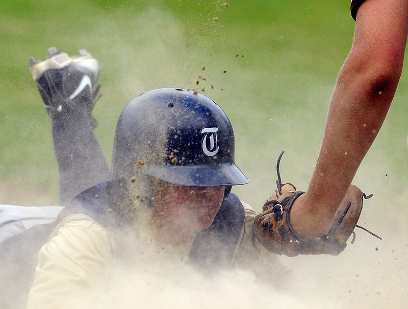 Brandon Metevier of Traip Academy stirs up dust with a headfirst slide and beats a tag by Monmouth Academy third baseman Josh Fournier during Monmouth's 12-5 victory Tuesday.