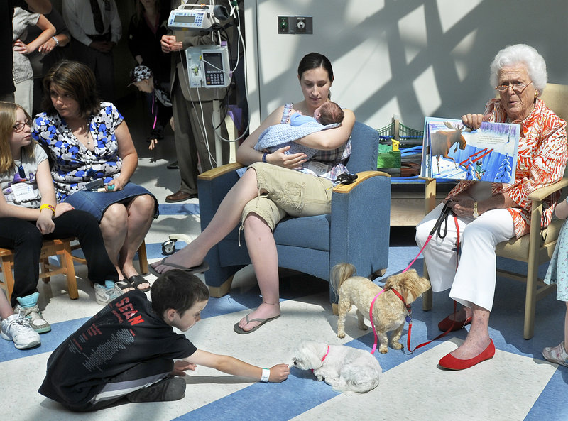 Former first lady Barbara Bush reads to children at Maine Medical Center on Wednesday while Sean Moriarty of Eliot plays with Mrs. Bush's dogs, Bibi and Mini Me. Mrs. Bush was on hand to read a story to young patients to celebrate her 86th birthday.