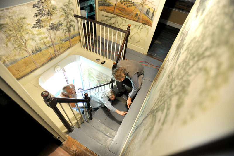 Preservationists examine some of the art in the narrow stairwell.