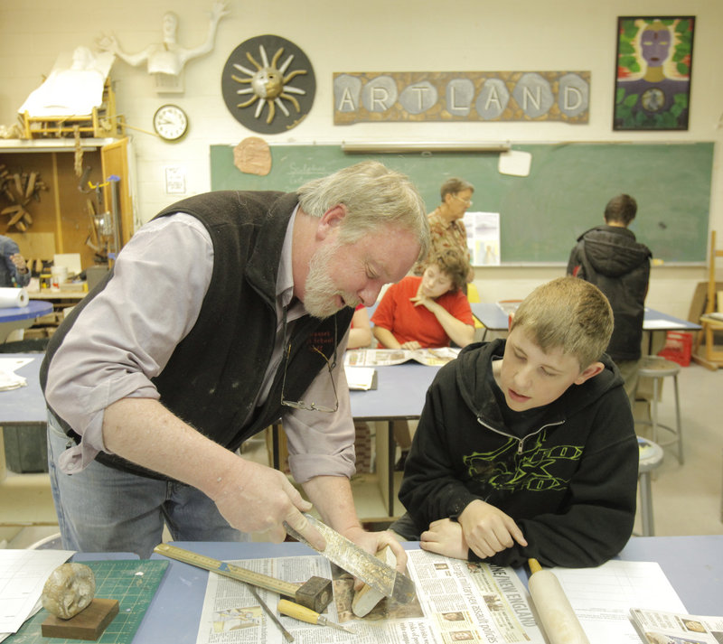 Thomas Block teaches freshman Derek Flowers how to use a rasp file to sculpt soapstone at Wiscasset High School.