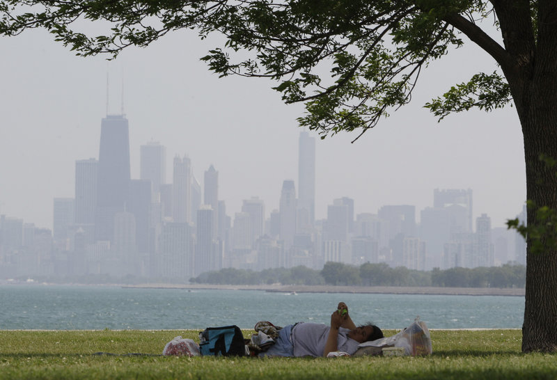 A woman cools off in the shade of a tree Wednesday at Montrose Beach in Chicago, where the temperature peaked at 94 degrees. The city's record for the date is 97, set in 1933.