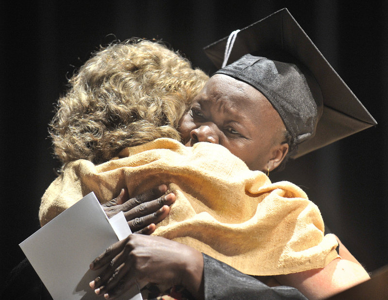 Portland Adult Education staff member Valerie deVuyst shares a hug with graduate Lia Boulis Kodi after presenting her an achievement award at Thursday night's graduation ceremony held at Portland's Merrill Auditorium. Graduates ranged in age from 18 to 68.