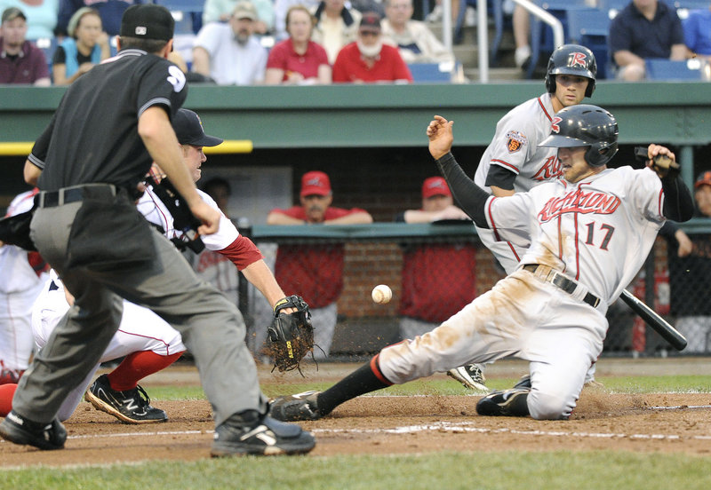 Justin Christian of the Flying Squirrels slides safely into home as Sea Dogs pitcher Alex Wilson awaits a late throw from catcher Ryan Lavarnway in Richmond's 7-2 victory.