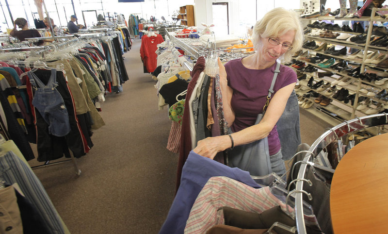 "Sarah Harriman of Bath looks over clothes at the Catholic Charities Thrift Store in Portland on Tuesday. ""I've been thrift store shopping since the '70s, and this is a good one ... clean and neat with good-quality merchandise,"" she said."