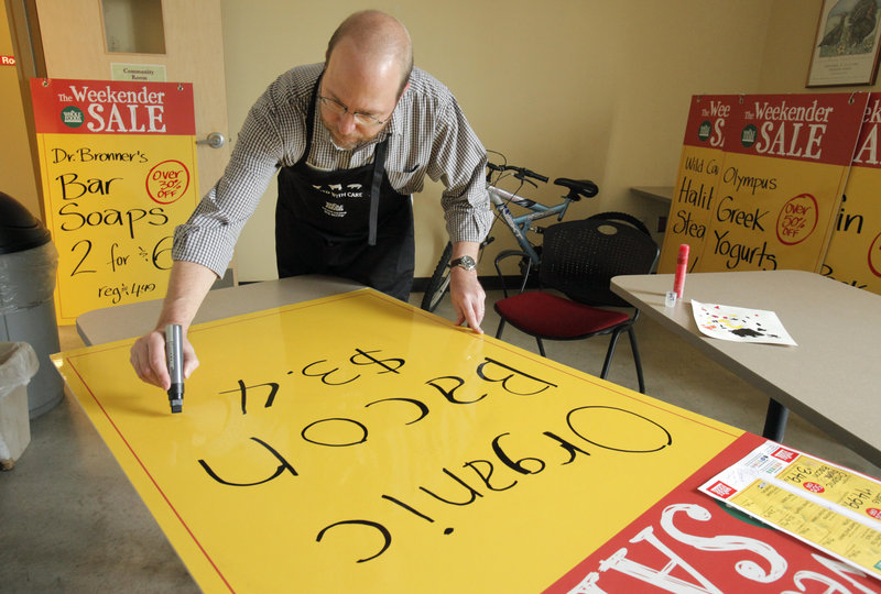 Ray Routhier works on a sign advertising organic bacon at Whole Foods Market in Portland. The large signs are hung in the windows of the store so passers-by can see them.