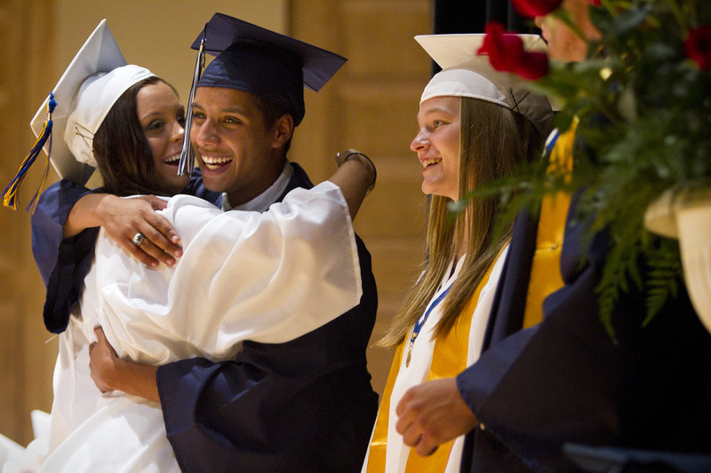 Westbrook Class President Joshua Hand hugs classmate McKenzie Johnson during the school's commencement ceremony at Merrill Auditorium in Portland on Friday. To their right is Class Marshal Vanessa Bradbury.