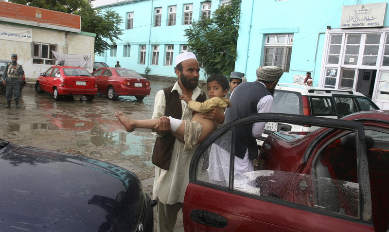 An Afghan man carries a child injured in a bombing that killed another child Saturday. The suicide blast was carried out by an attacker pushing an ice cream cart.