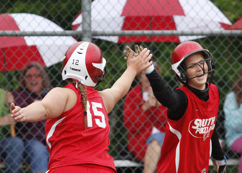 South Portland's Olivia Indorf, left, and Danica Gleason celebrate Saturday after scoring on Amanda Linscott's first-inning double in a 14-2 victory against McAuley.