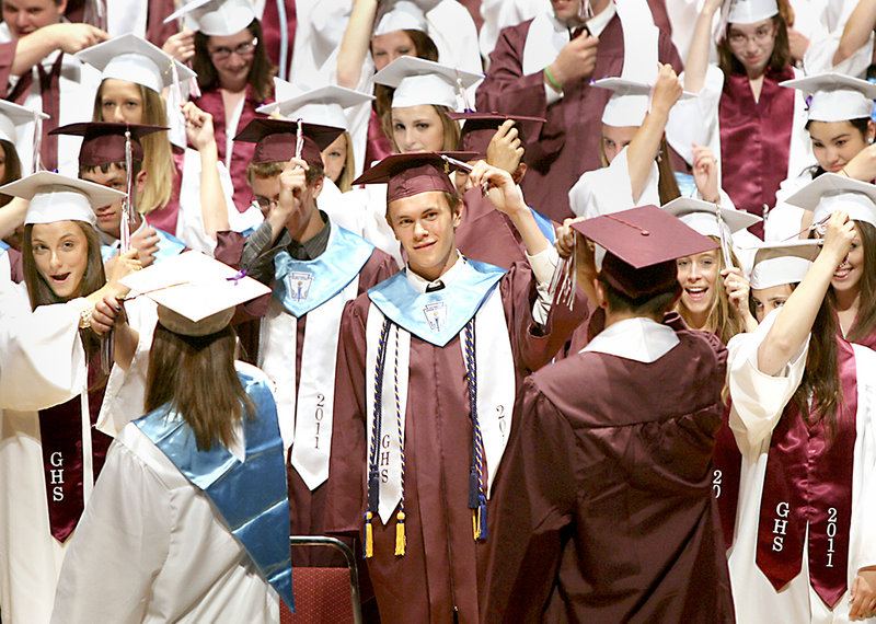 Andrew Ernest, center, turns his tassel in the midst of his fellow Gorham High graduates Sunday.