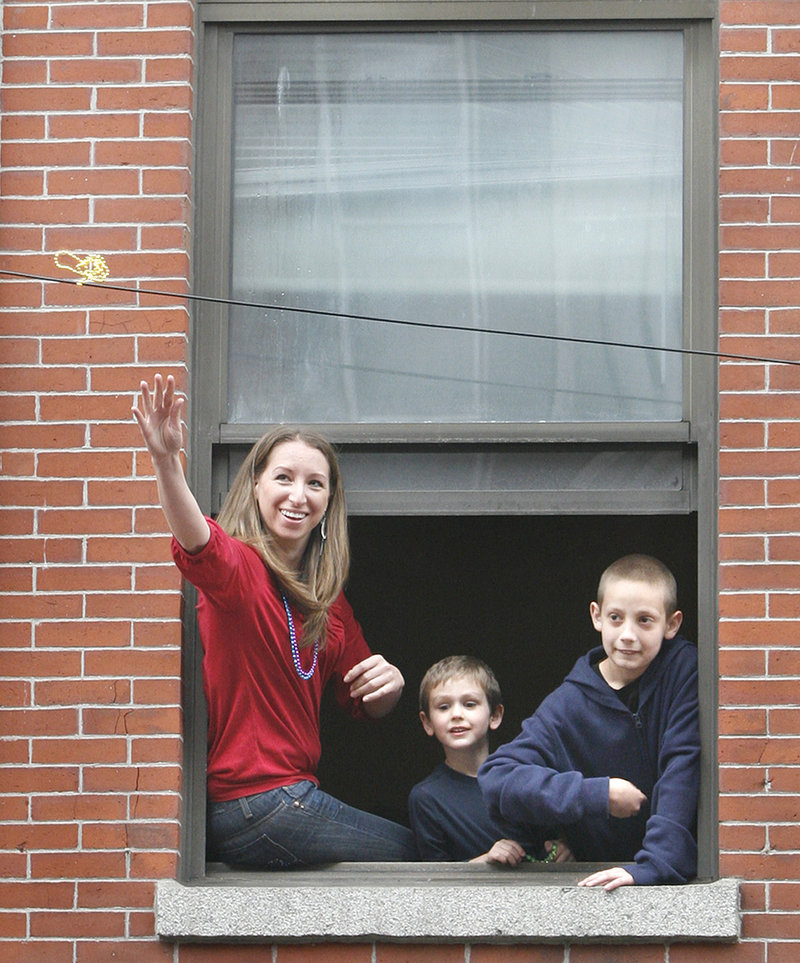Jennifer Eagan throws beads from her apartment down to people on Exchange Street with the help of Drew Gannon, middle, and his brother Travis.